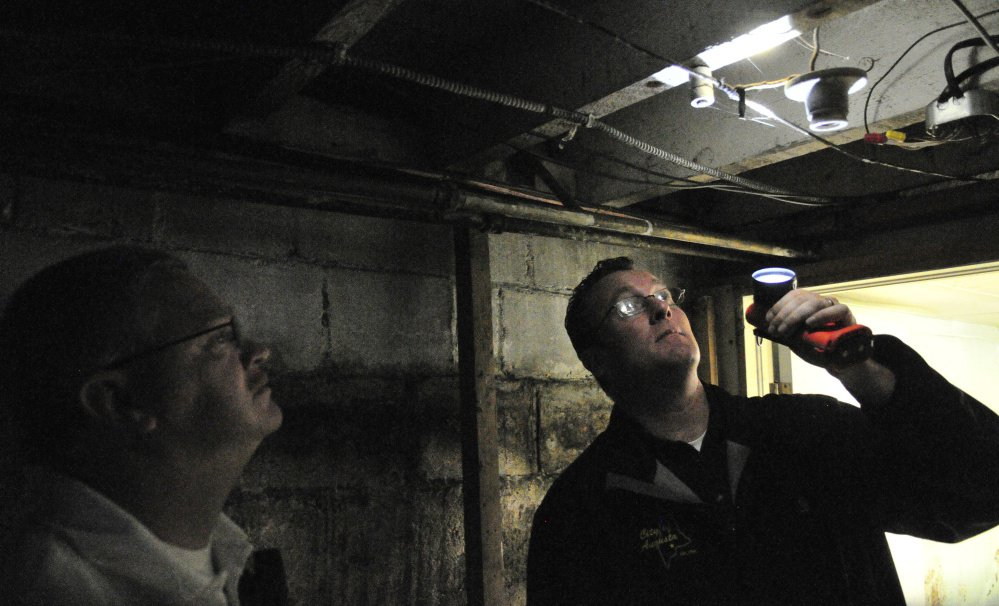 City of Augusta Code Enforcement Officer Robert Overton and Deputy Fire Chief David Groder look at wiring during an inspection on Oct. 2 of an apartment building.