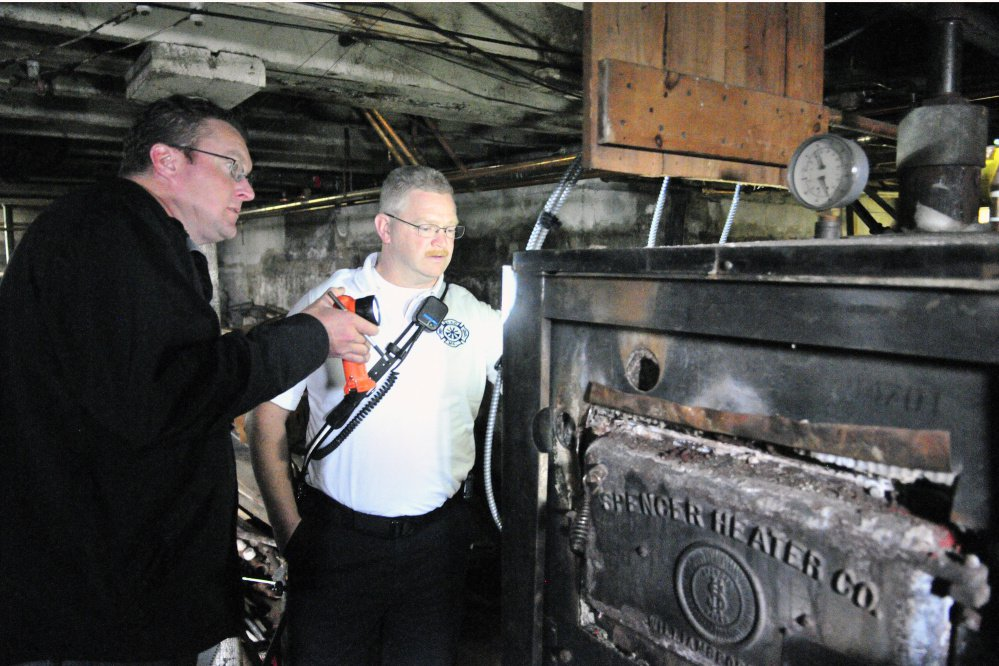 City of Augusta Code Enforcement Officer Robert Overton and Deputy Fire Chief David Groder look at an old heating system during an Oct. 2 inspection of an apartment building.