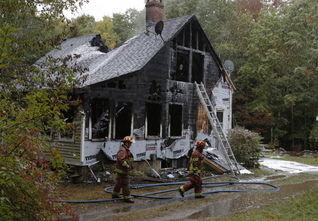 Firefighters walk past the house that burned Sunday morning in Boothbay. Two people died and four others were injured in the fire. Joel Page/Staff Photographer