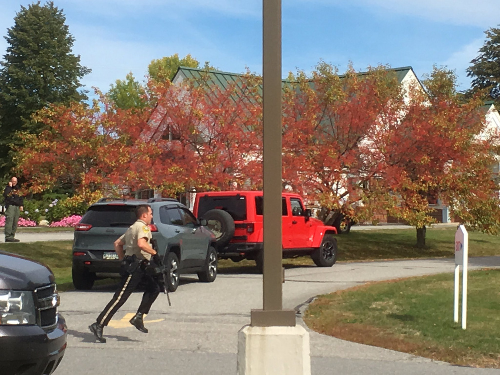 A Kennebec County sheriff's deputy runs across a driveway Friday at the Camden National Bank in Manchester as police look for a bank robbery suspect.