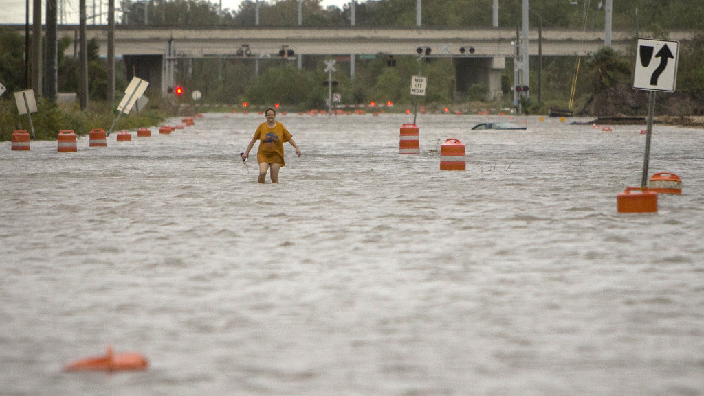 A woman walks along flooded President Street in Savannah, Ga., after leaving her homeless camp during Hurricane Matthew on Saturday. Associated Press/Stephen B. Morton