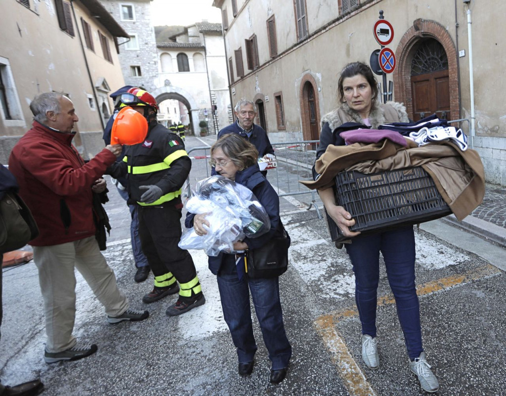 Residents carry some of their belongings in the small town of Visso in central Italy Thursday, after a 5.9-magnitude earthquake destroyed part of the town. A pair of strong aftershocks shook central Italy late Wednesday, crumbling churches and buildings, knocking out power and sending panicked residents into the rain-drenched streets just two months after a powerful earthquake killed nearly 300 people. <em>Associated Press/Alessandra Tarantino</em>