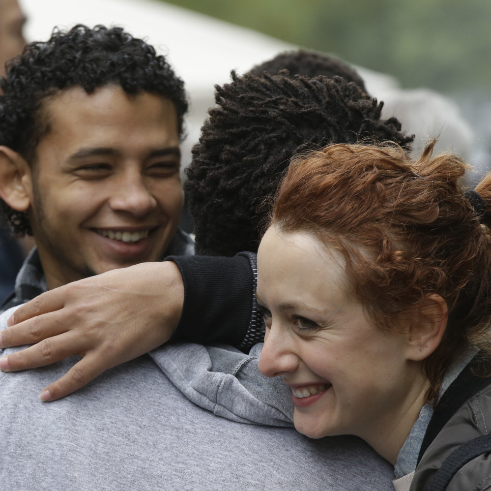 Migrants and citizens dance and hug each other in Milan on Tuesday. More than 1,000 Italians attended a party for about 80 migrants.