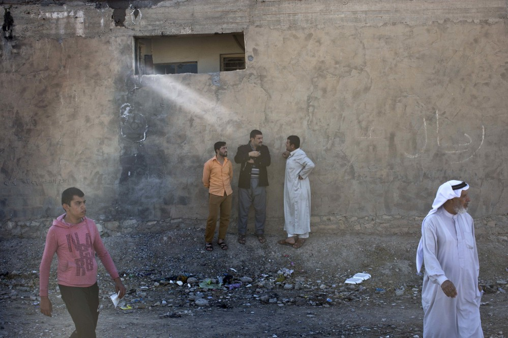 People gather on a street in Gogjali, an eastern district of Mosul, Iraq, on Thursday.