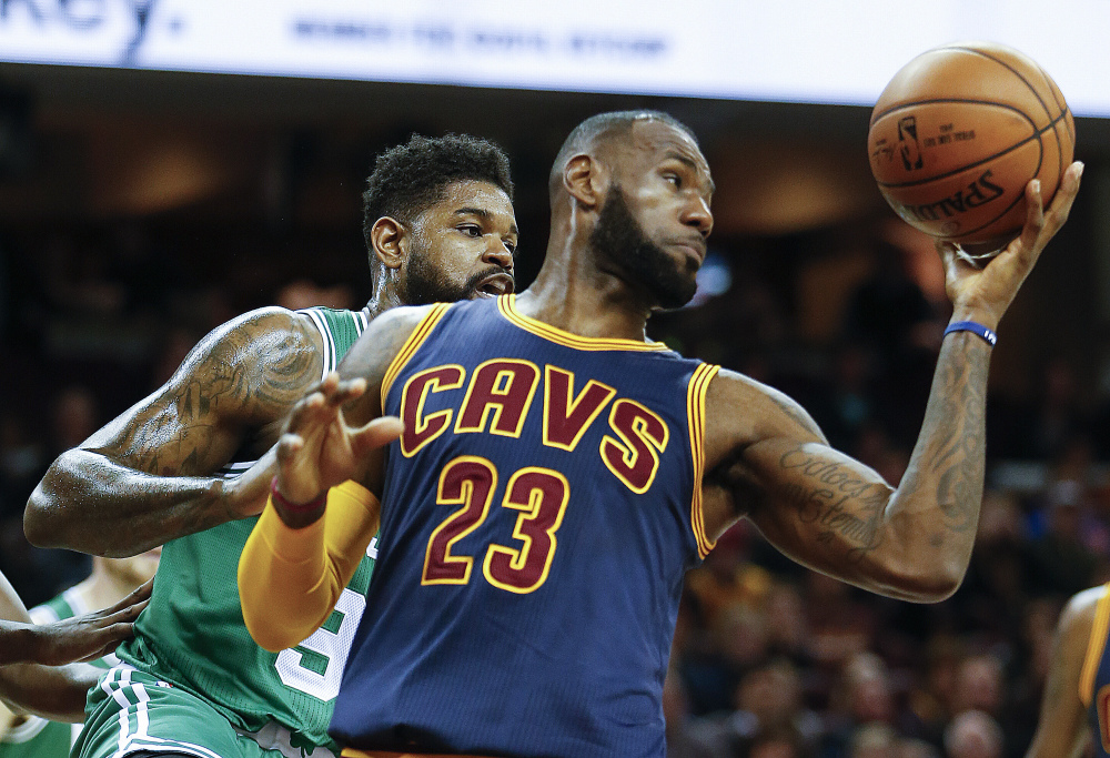 LeBron James grabs a rebound against Boston's Amir Johnson in the first half Thursday night in Cleveland.