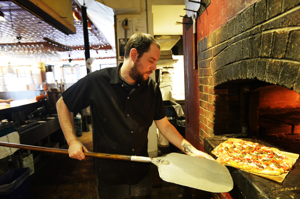 Jon Cogswell, a chef at Bonobo in Portland, takes a pizza out of the brick oven on Nov. 2.