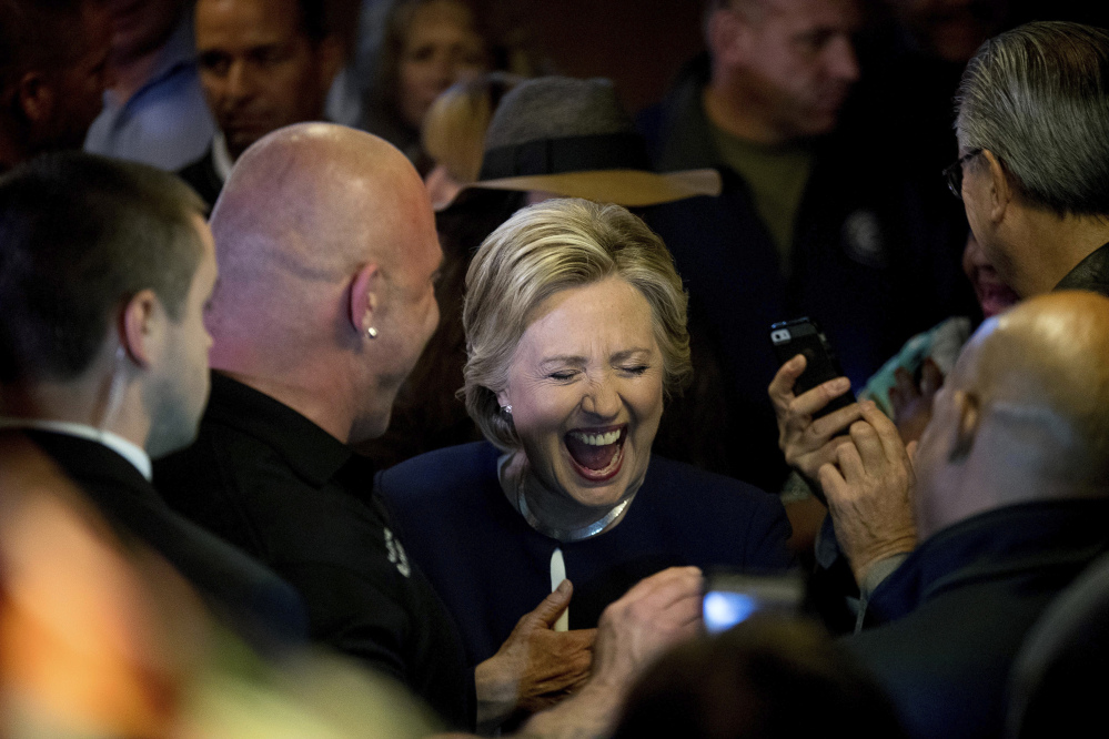 Democratic presidential candidate Hillary Clinton laughs while talking with patrons at Miller's Bar in Dearborn, Mich., on Friday.