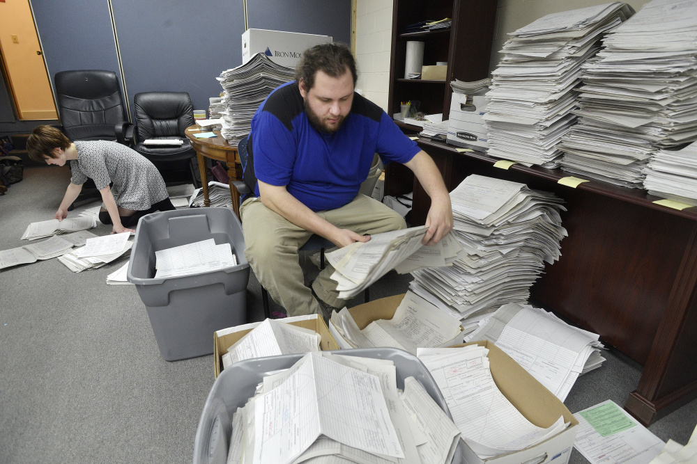 Staff and volunteers  for the marijuana legalization campaign are sorting petitions at their office in Falmouth. Office manager Shaun Bowen and volunteer Allison Cormier organize stacks of petitions at their headquarters.