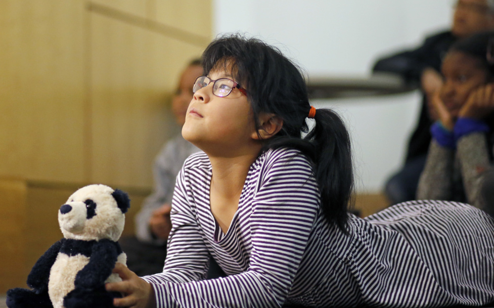 Ten-year-old Eleanor Lo (with Panda the panda) listens to illustrator Ashley Bryan during an appearance at Portland Public Library to promote his book,