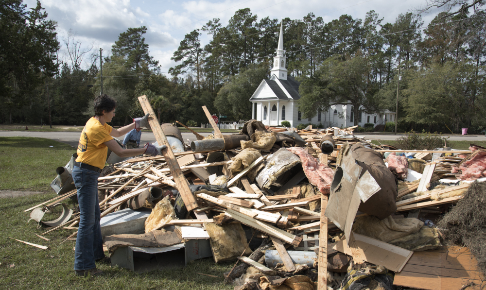 Wendy Gable, with Southern Baptist Convention Disaster Relief, throws wood on a pile from a home that was heavily damaged by floodwaters from Hurricane Matthew in Nichols, S.C.
