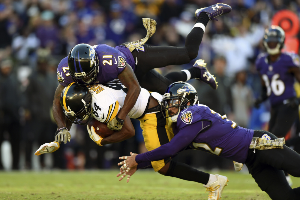 Steelers receiver Antonio Brown is brought down by Ravens safeties Lardarius Webb, top, and Eric Weddle during Sunday's game in Baltimore. Despite losses in their previous four games, the Ravens moved into a tie with Pittsburgh atop the AFC North standings with a 21-14 victory.