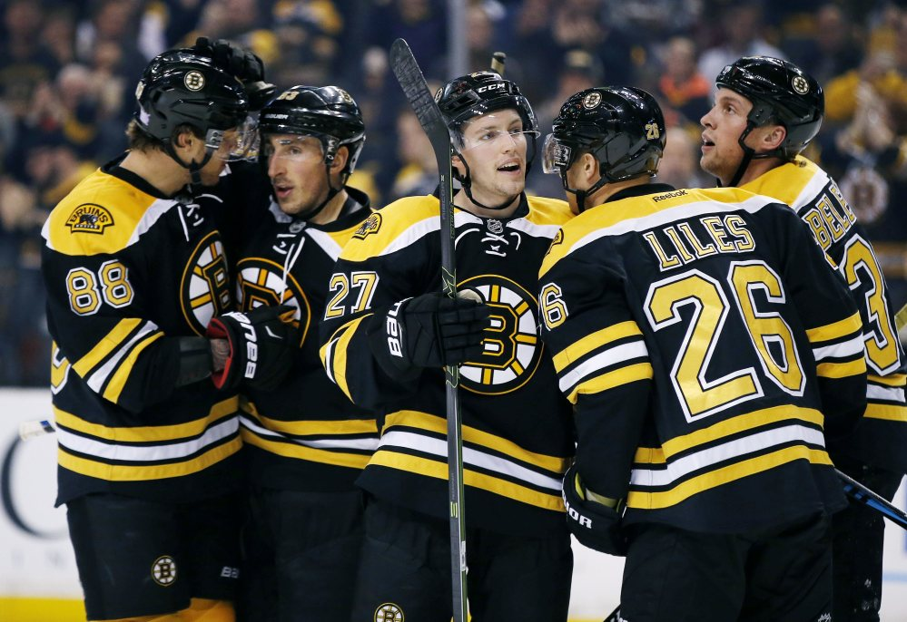 From left, Bruins David Pastrnak, Brad Marchand, Austin Czarnik, John-Michael Liles and Matt Beleskey celebrate Marchand's goal in the second period Monday night in Boston. The Bruins went on to a 4-0 win.