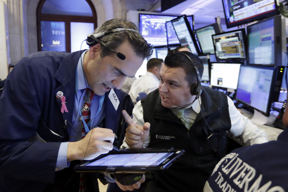 Traders Gregory Rowe, left, and Robert Finnerty work on the floor of the New York Stock Exchange on Wednesday. Stocks started to move higher in midday trading after futures plunged Tuesday night on the prospect of a Trump victory.