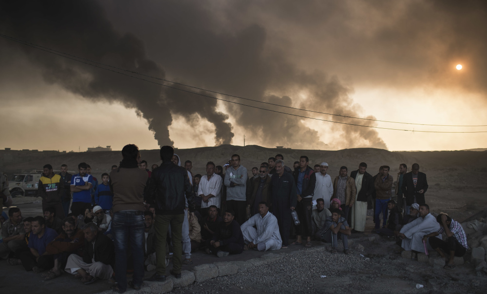 Men are held by Iraqi national security agents, to be interrogated at a checkpoint, as oil fields burn south of Mosul, Iraq, last Saturday. Islamic State fighters launch counterattacks in the thin strip of territory Iraqi special forces have recaptured in eastern Mosul, highlighting the challenges ahead as the battle moves into more densely populated neighborhoods.
