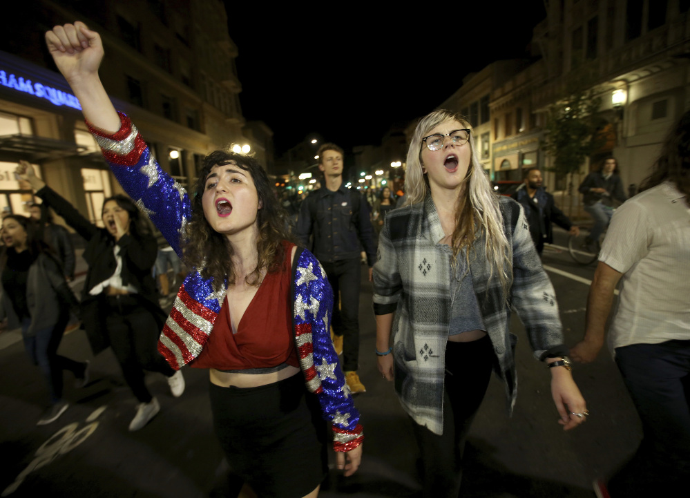 Madeline Lopes, left, and Cassidy Irwin, both of Oakland, Calif., march with other protesters in downtown Oakland early Wednesday in one of several demonstrations across the country.