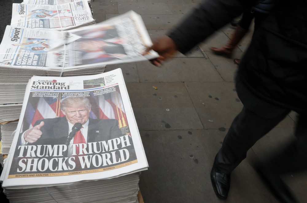 A passer-by takes a copy of the Evening Standard, the local free newspaper in London. NATO allies now wonder whether Donald Trump will keep his pledge on conditional protection.