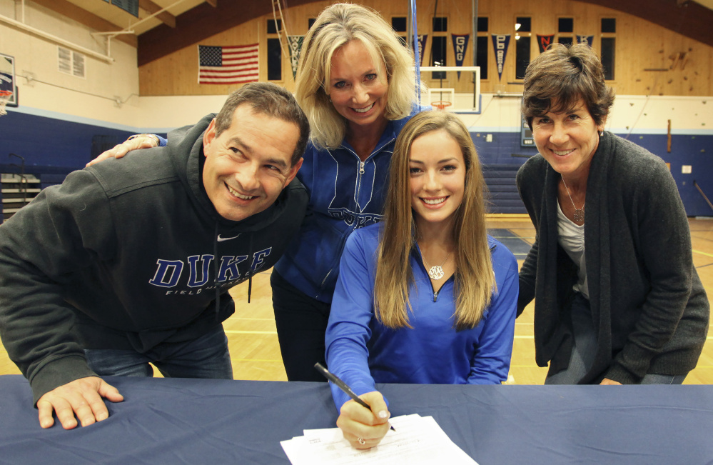 Lily Posternak of York, who will play field hockey at Duke, is joined Wednesday by her parents, Dan and Kristin, and York Coach Barb Marois as she signs her letter of intent.