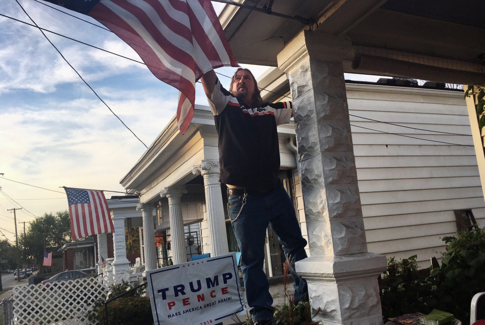 Terry Wright, 59, a retired union painter, adjusts the U.S. flag on the porch of his Louisville, Ky., home on Tuesday. Wright, a registered Democrat backing Republican presidential candidate Donald Trump, says he has given up on his old party.