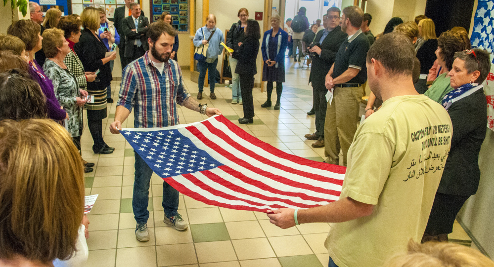 Nursing students Chad Ceccarini, left, an Air Force veteran, and Nicholas Whitmore, an Army veteran, fold a flag during a Veterans Day ceremony Thursday in the Randall Student Center at the University of Maine at Augusta. The flag was presented to nursing instructor Patricia Day and will be displayed in a nursing classroom. Cards written by students were presented to veterans, along with ice cream and cake at the event.