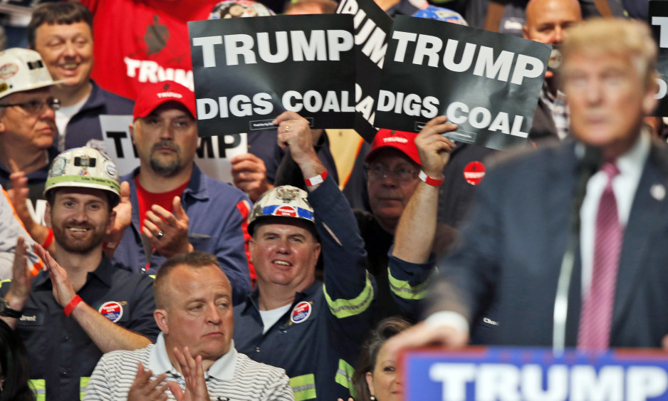 Coal miners wave signs as Republican presidential candidate Donald Trump speaks during a May rally in Charleston, W.Va. Trump's election could signal the end of many of President Obama's signature environmental initiatives.