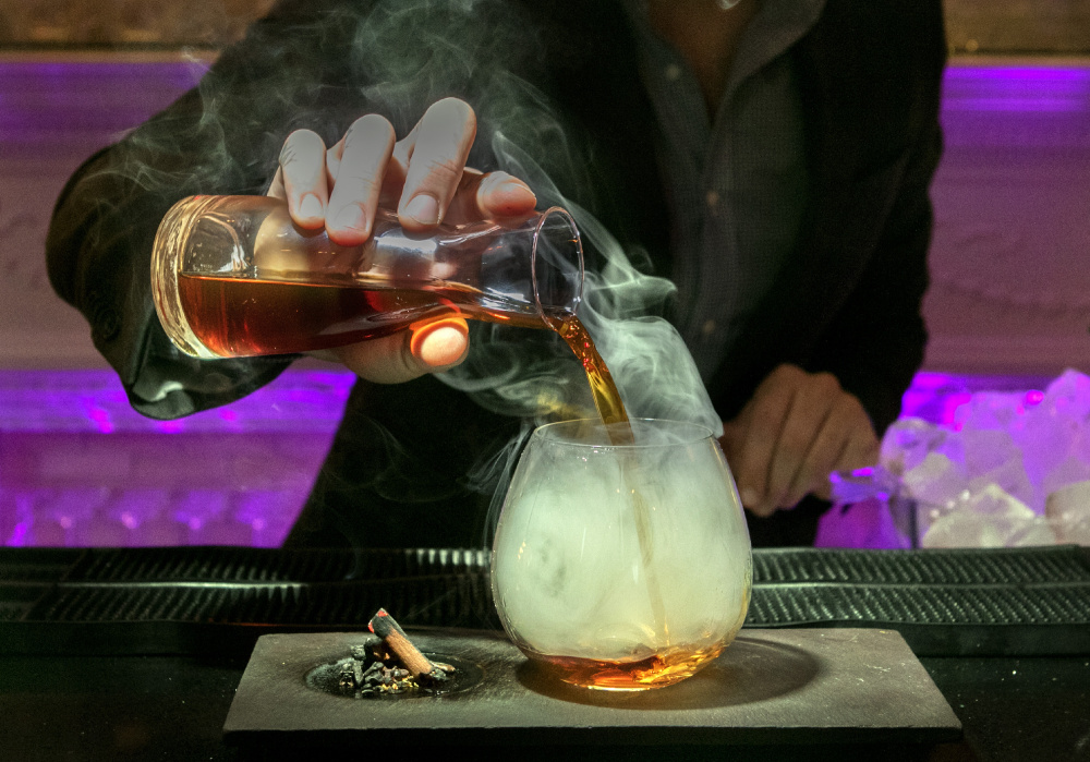 Trevin Hutchins pours a Jakarta, made with Knob Creek Rye, Averna, Cynar, Carpano and Coastal Root bitters, and the glass is smoked with Chinese Five Spice.