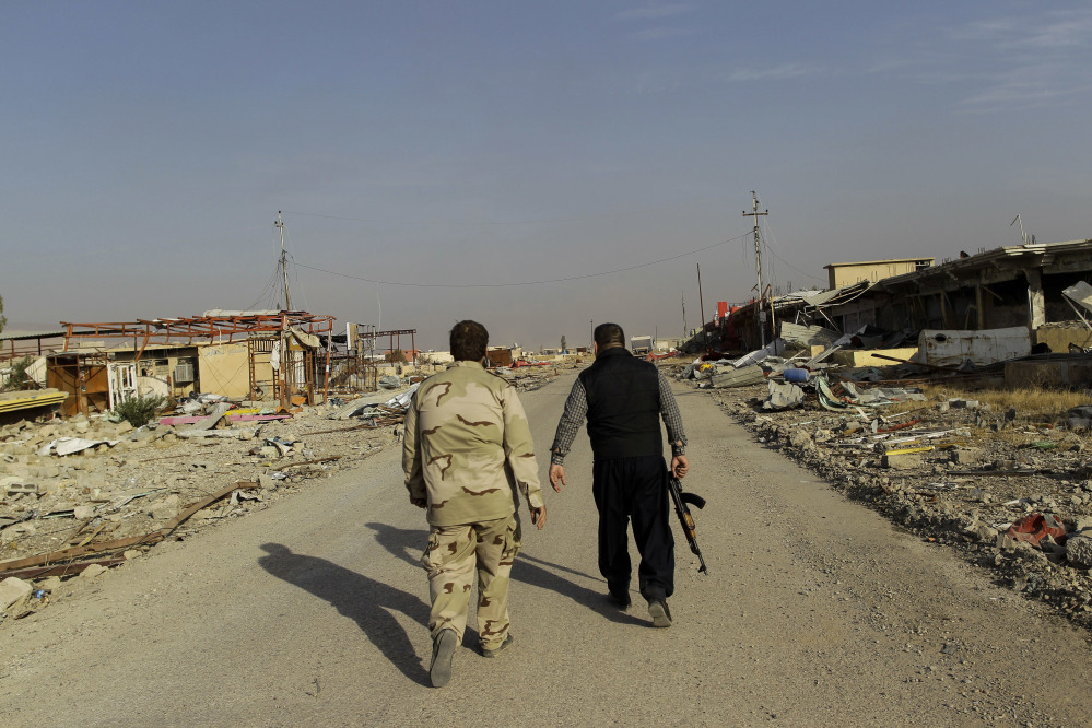 Ali Hussein, right, and his son walk to check on the family's used car business, which was looted by Islamic State fighters and destroyed in fighting to oust them in Bashiqa, east of Mosul, Iraq, on Friday.