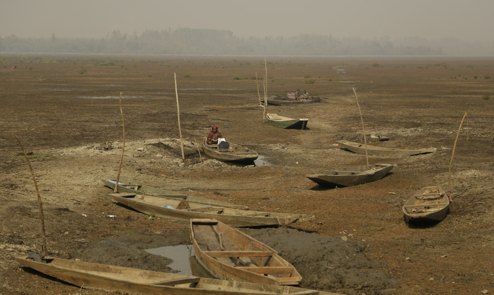 A Kashmiri woman sits inside a boat in a dried portion of Wular Lake in Indian-controlled Kashmir. India has realized that the vast, alpine lake would be worth more if it were pristine than exploited for resources.