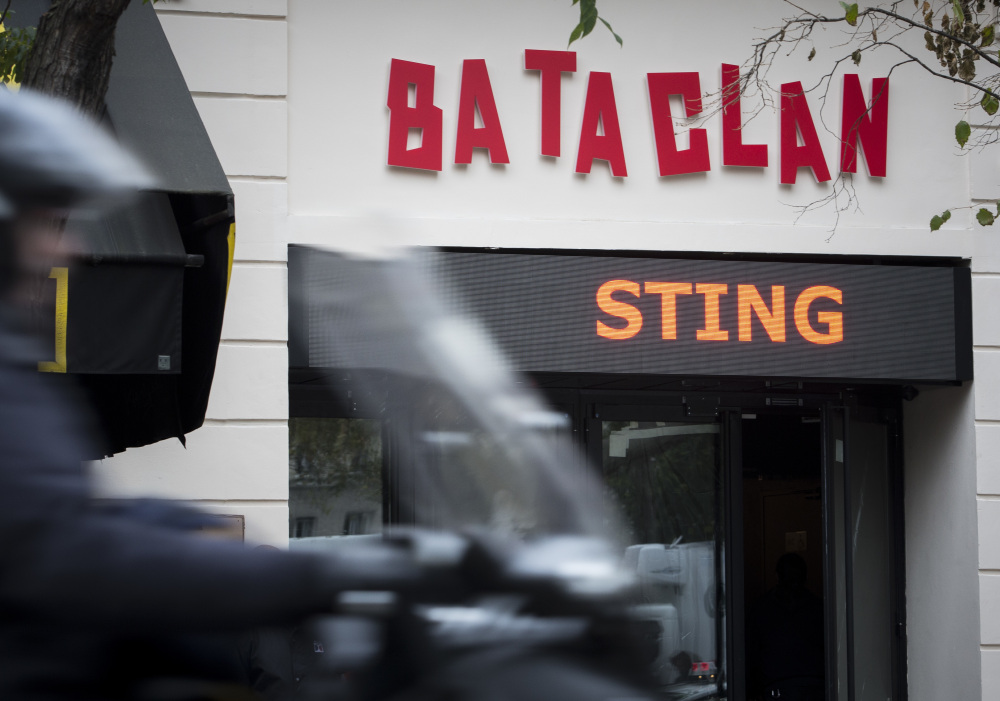 A man rides a scooter past the Bataclan on Saturday.  Proceeds from Sting's concert will go to charities aiding survivors of last year's terror attack.
