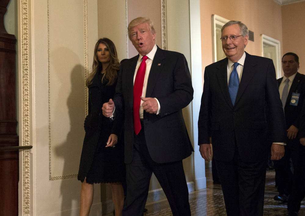 President-elect Donald Trump, accompanied by his wife, Melania, and Senate Majority Leader Mitch McConnell of Ky., walks on Capitol Hill in Washington.
