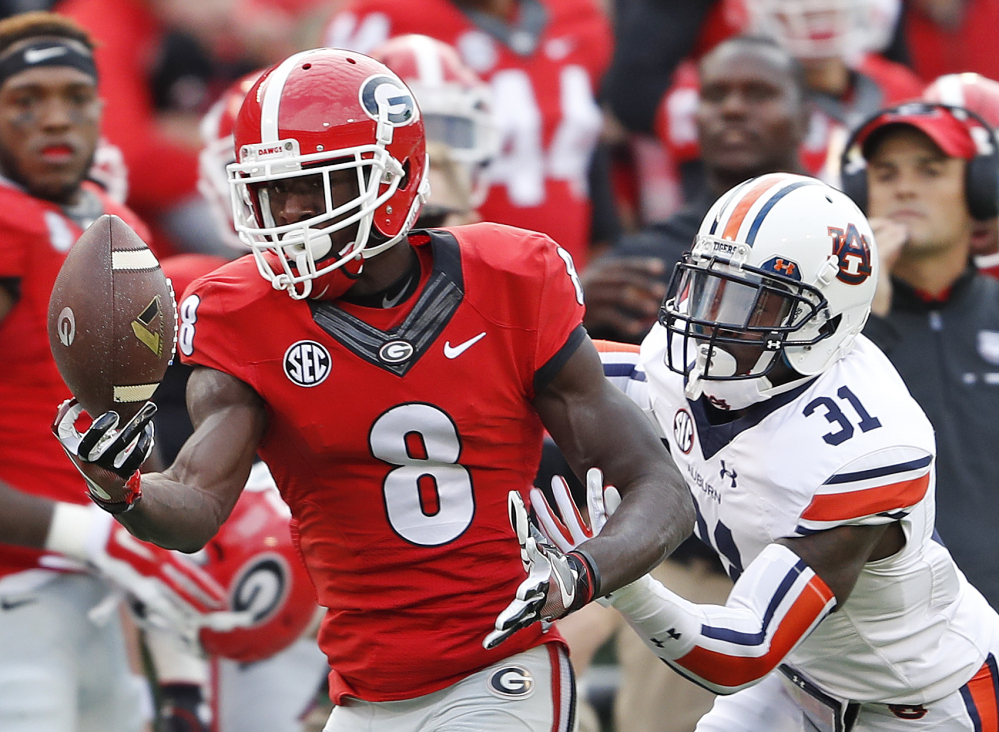 Georgia wide receiver Riley Ridley, left, makes a catch as Auburn defensive back Javaris Davis defends in the first half Saturday in Athens, Georgia. The Bulldogs upset No. 8 Auburn, 13-7.