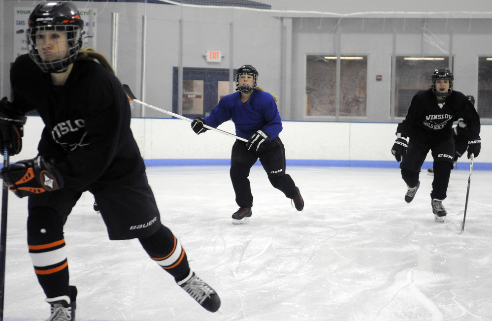 Members of the Winslow/Gardiner girls hockey team skate during practice last Wednesday at the Ice Vault in Hallowell.