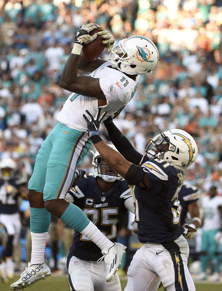 Miami Dolphins wide receiver DeVante Parker catches a pass over San Diego Chargers strong safety Adrian Phillips during the second half of an NFL football game in San Diego, Sunday. Associated Press/Denis Poroy