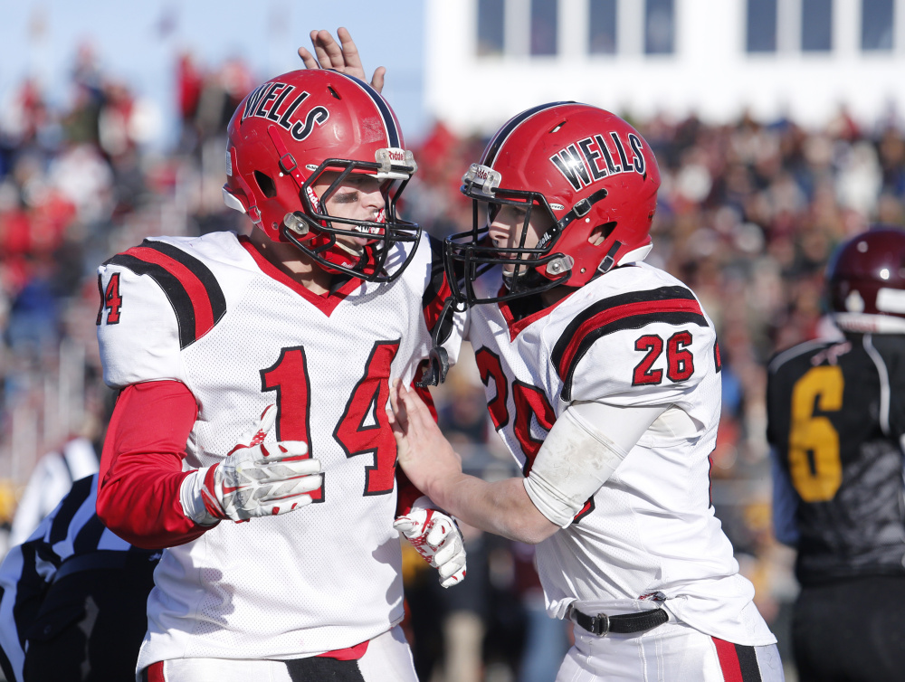 Riley Dempsey of Wells gives his teammate Jordan Cluff a pat on the helmet after Cluff picked up a big first down in the fourth quarter of Saturday's regional championship game at Cape Elizabeth. Wells was motivated by losses in the regional finals in the last two seasons.