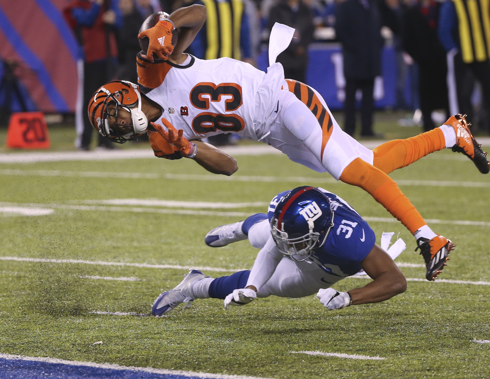 Bengals wide receiver Tyler Boyd dives over Giants cornerback Trevin Wade for a touchdown in the third quarter of New York's 21-20 win Monday in East Rutherford, N.J.