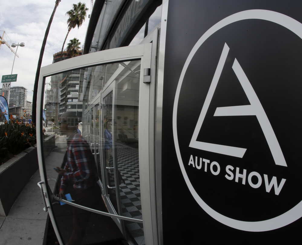 A visitor leaves a display at the Los Angeles Auto Show, where automakers are offering even fewer models with a manual transmission. The full show begins Friday.