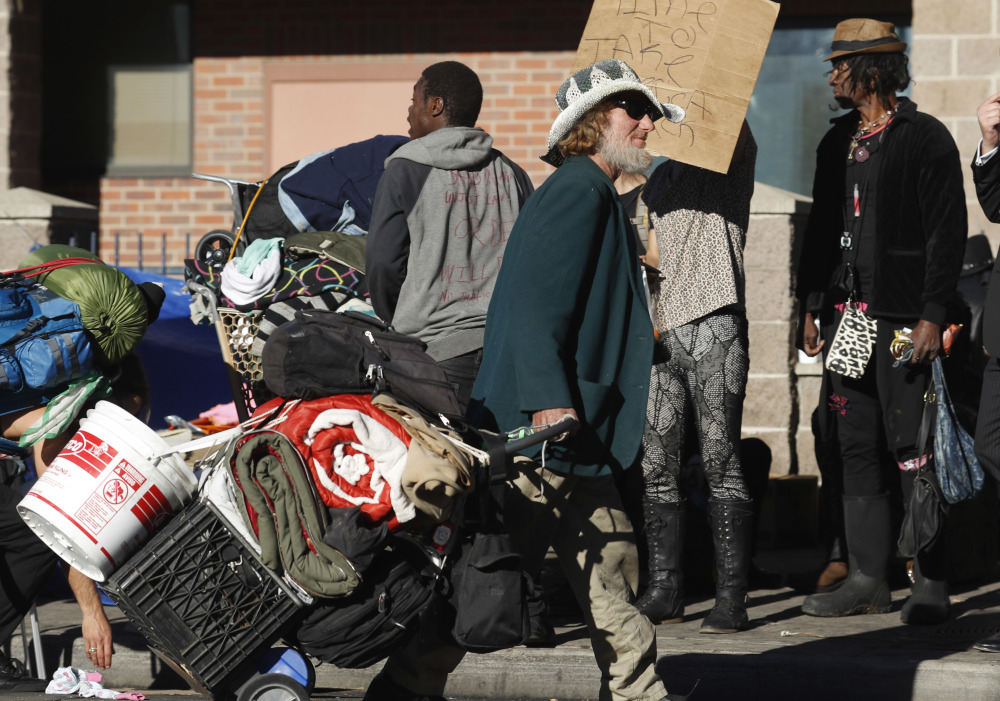 A man drags his belongings during a police sweep of homeless people living on the sidewalks near a shelter in downtown Denver on Tuesday.