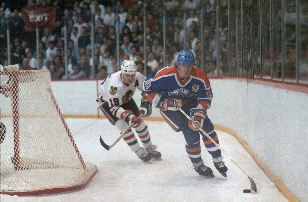 Edmonton Oilers'  Wayne Gretzky (99) carries the puck behind the net in a game against the Chicago Black Hawks in 1987. Gretzky will lend his voice to a character in 'The Simpsons.'