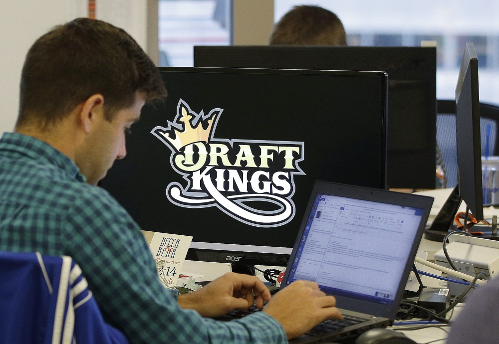 Bear Duker, a marketing manager for strategic partnerships at DraftKings, works at his computer last fall at the company headquarters in Boston. Daily fantasy sports rivals DraftKings and FanDuel have agreed to merge.