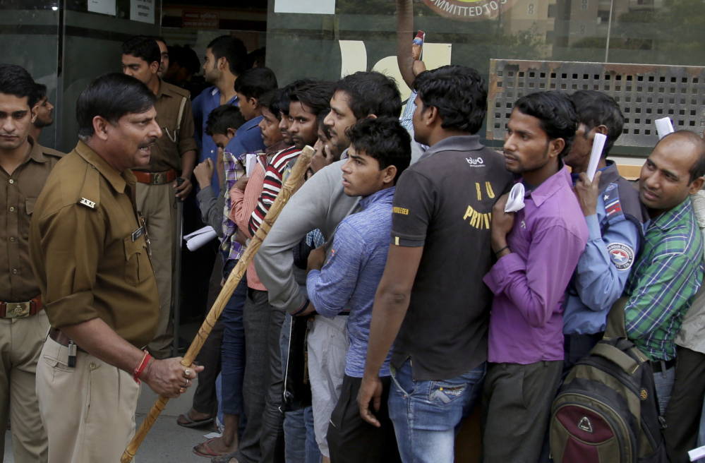 An Indian police officer warns people to stay in line as they wait to exchange or deposit discontinued currency notes at a bank on the outskirts of New Delhi, India, on Tuesday.