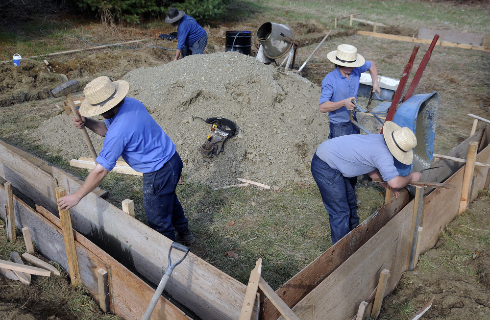 Levy Miller, left, Mose Miller and Jacob Yoder pour concrete as their uncle, John Miller, mixes it for the work shed that Mose Miller is building at the residence he purchased in Whitefield. Mose Miller and several Amish relatives are moving to Whitefield.