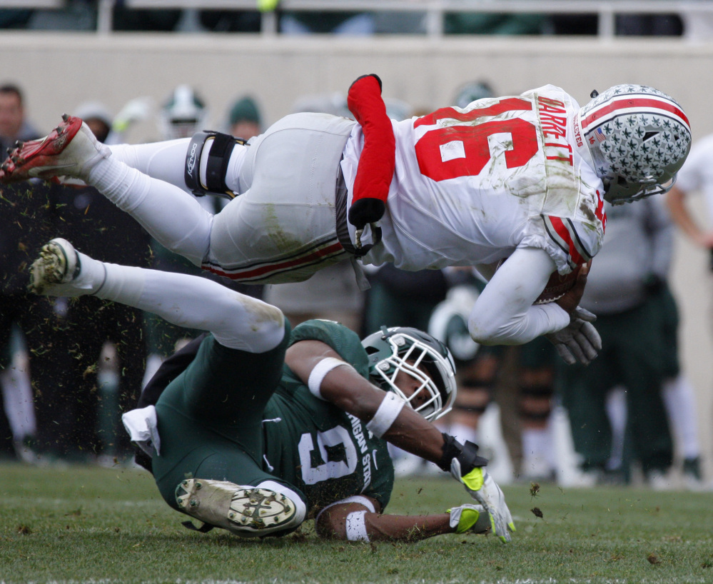 Quarterback J.T. Barrett is upended by Montae Nicholson of Michigan State during the second quarter of second-ranked Ohio State's 17-16 victory Saturday. The Buckeyes meet Michigan in a showdown next Saturday.