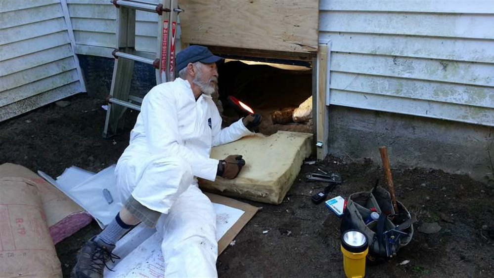 Dave Brown, 75, a volunteer for the Harpswell Aging at Home team, insulates the floor under a house in coastal Maine. Volunteers in the graying state are helping seniors remain in their homes.