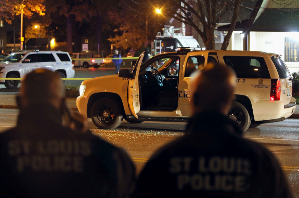 Police officers inspect a truck undercover police officers were riding in when it was shot through the windshield by a suspect they were following in St. Louis on Monday. The police and man engaged in a shootout that ended with the suspect being fatally shot.