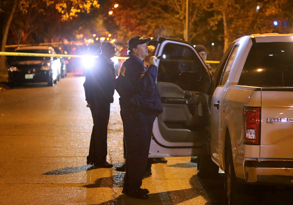 Police officers inspect a truck undercover police officers were riding when it was shot through the windshield by a suspect they were following in the 6500 block of Smiley Avenue Monday, Nov. 21, 2016, in St. Louis. The police and man engaged in a shootout in the neighborhood that ended with the suspect being fatally shot. The man who police shot is suspected of shooting a police officer earlier in the night and several other crimes in both St. Louis County and St. Louis city. (David Carson//St. Louis Post-Dispatch via AP)