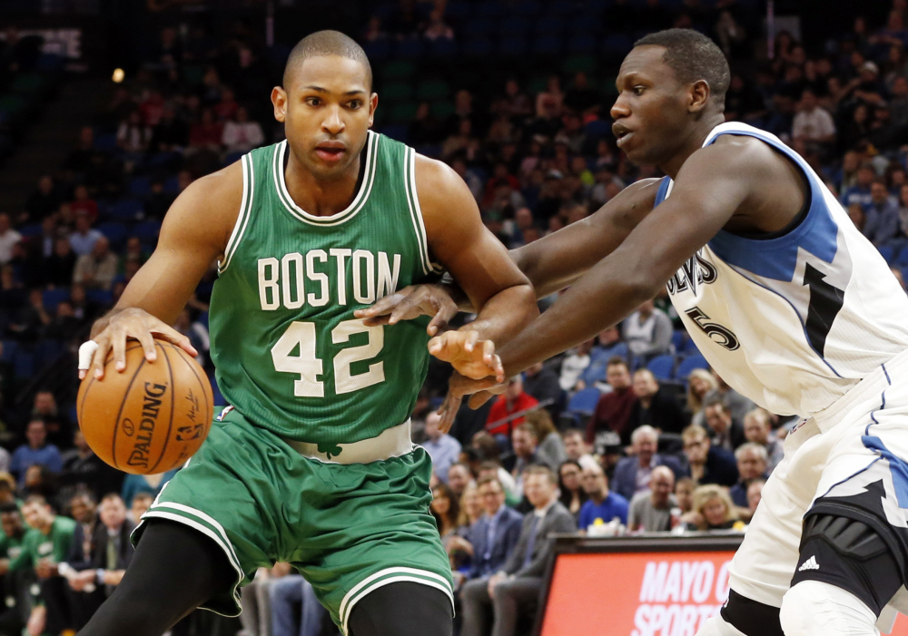 The Timberwolves' Gorgui Dieng reaches for the ball as Al Horford of the Celtics drives in the first quarter. Horford scored 20 points in the win.