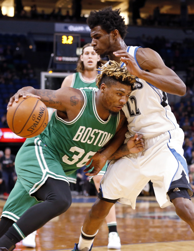 The Celtics' Marcus Smart drives into Minnesota's Andrew Wiggins in the first quarter of an Monday night's game in Minneapolis.