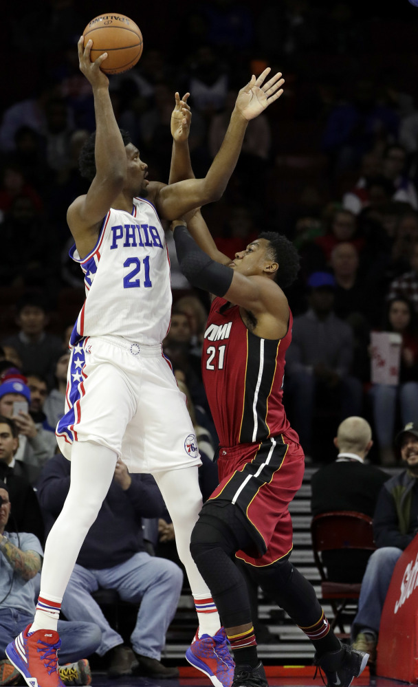 Philadelphia's Joel Embiid takes a shot while being defended by Miami's Hassan Whiteside during the 76ers' 101-94 win Monday.