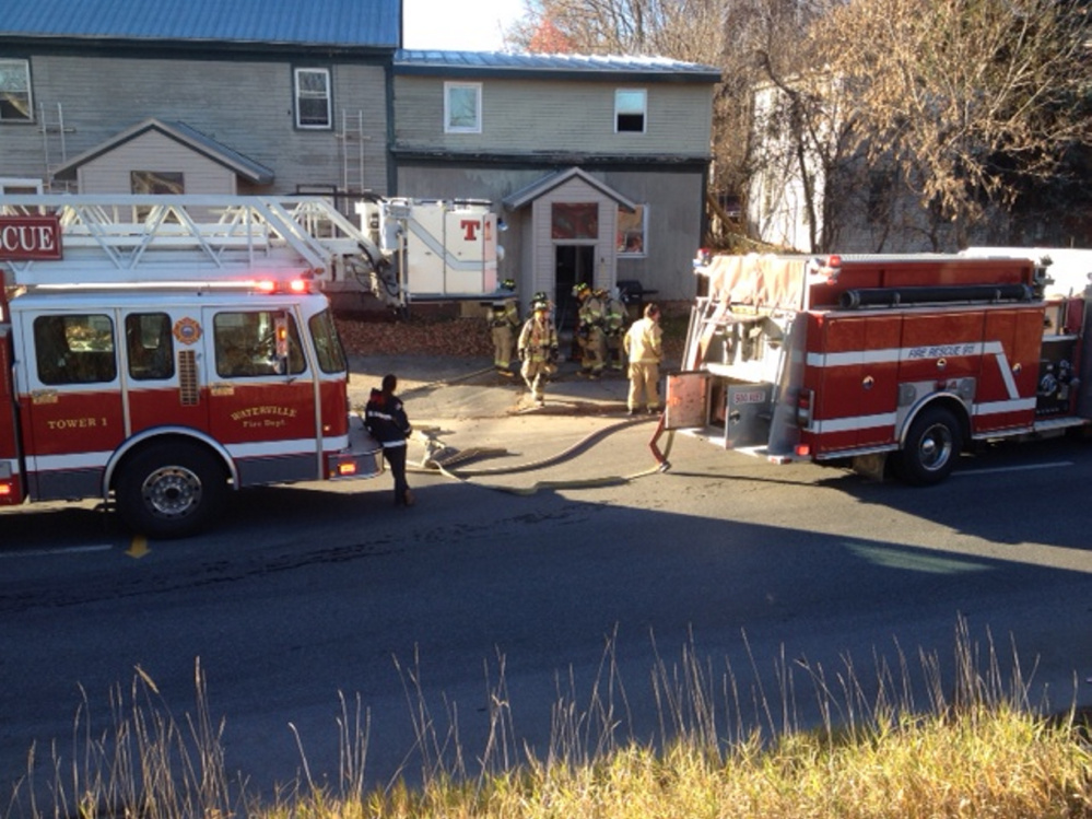 Firefighters work a fire Saturday at an apartment building on Front Street in Waterville that displaced tenant Cheryl Jack.