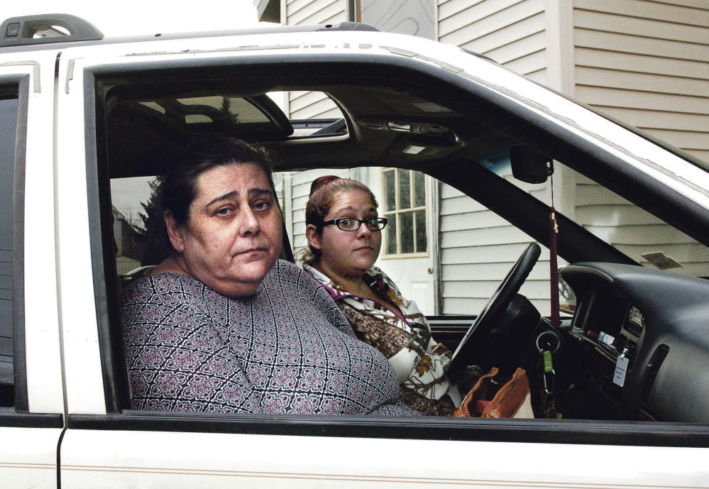 Apartment tenant Cheryl Jack, left, sits in a car on Monday outside the Waterville apartment from which she and her cat were rescued Saturday. Beside her is Crystal Hillman, a support staff employee with Assistance Plus.