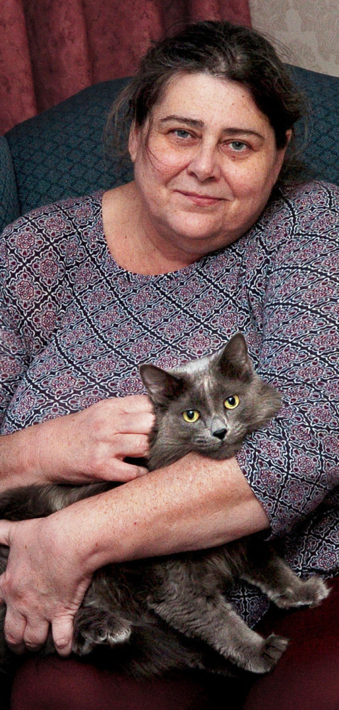 Cheryl Jack keeps her cat, Oliver Grey, close to her Tuesday. They they are reunited after a fire in their apartment on Saturday.